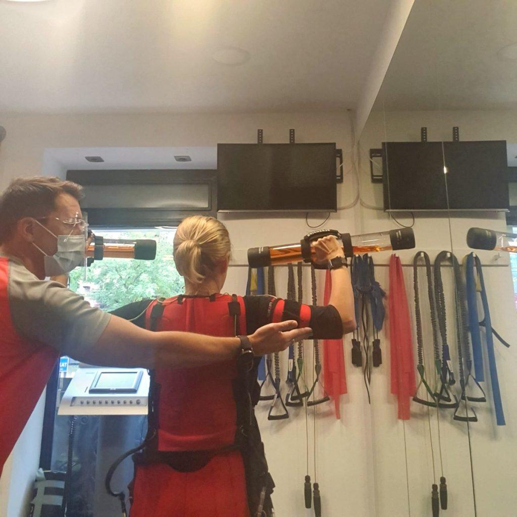 Prevenir lesiones deportivas en el entrenamiento   Imagen del gimnasio Firme20, mujer haciendo ejercicio con ayuda del entrenador personal.